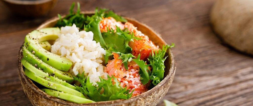 Hawaiian poke coconut bowl with grilled salmon fish, rice and avocado