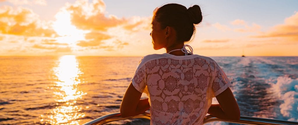 young girl enjoying the sunset from a cruise ship deck