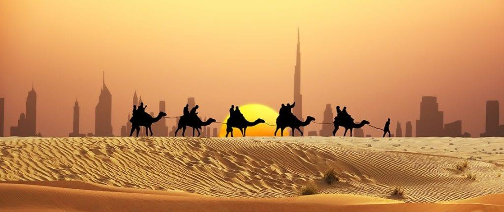 Desert safari caravan in front of Dubai skyline during sunset
