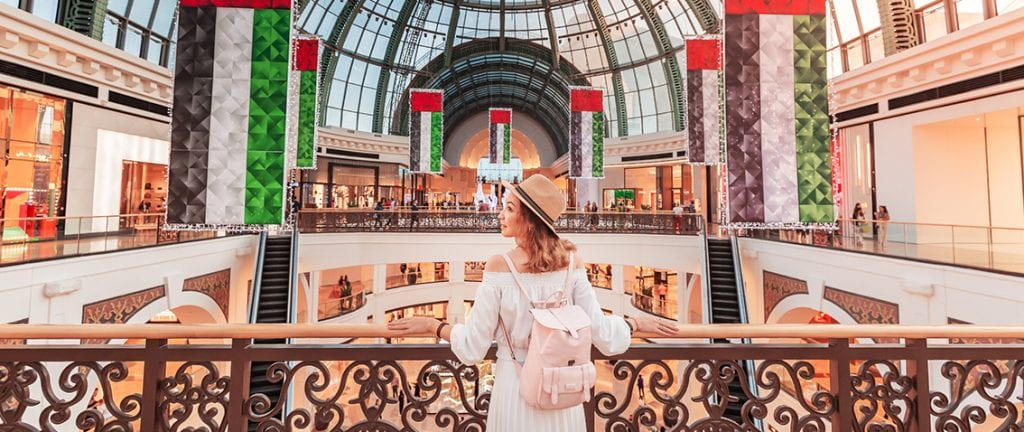 A young tourist walks through one of the largest shopping centers in Dubai - Emirates Mall. Travel in UAE concept