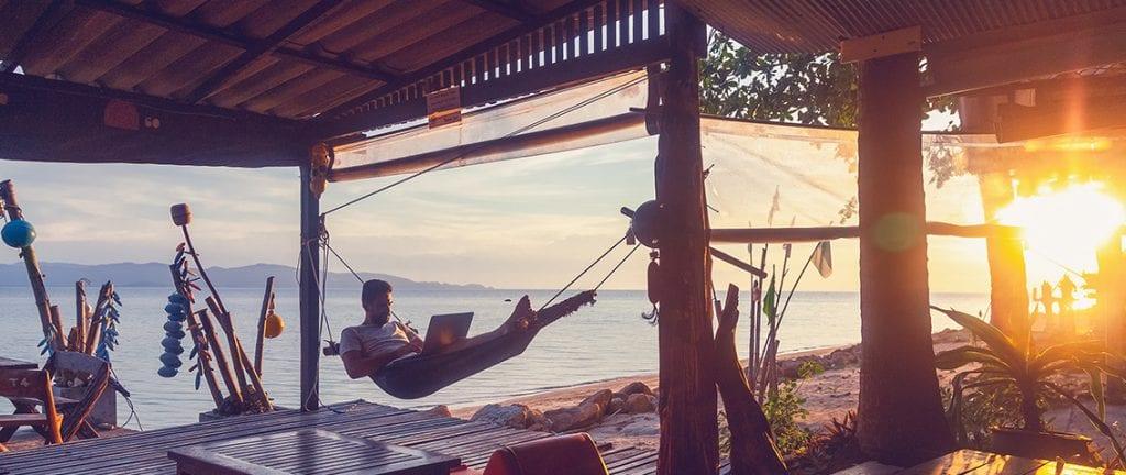 Digital nomad working on a hammock
