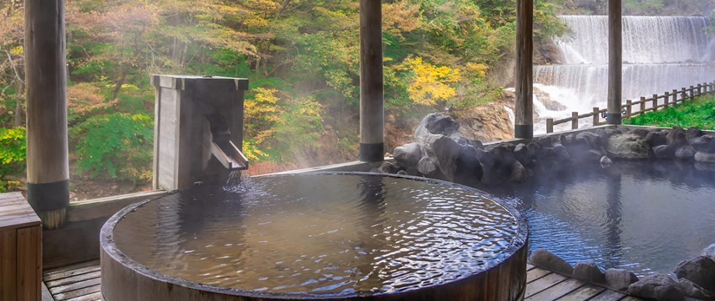 Japanese Hot Springs Onsen Natural Bath Surrounded by red-yellow leaves. In fall leaves fall in Fukushima, Japan